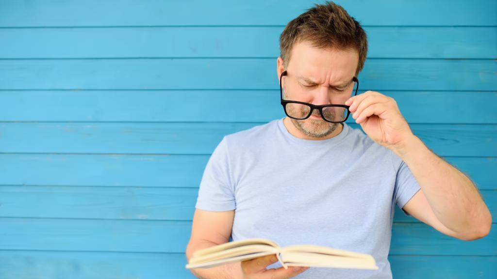 Mann schiebt Brille vor und versucht ein Buch zu lesen